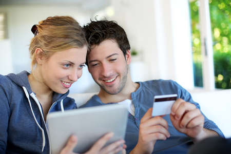 buying online: Happy young couple doing shopping on internet Stock Photo