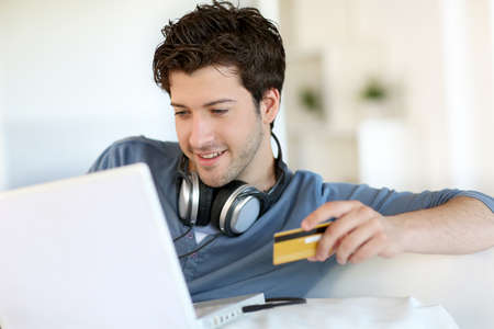 card payment: Young man buying music on internet with tablet