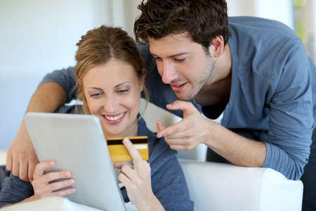 chicas comprando: Pareja joven en casa comprando en internet