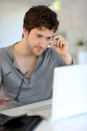 working from home: Young man studying from home
