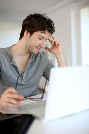 hombre estudiando: Joven estudiando desde su casa