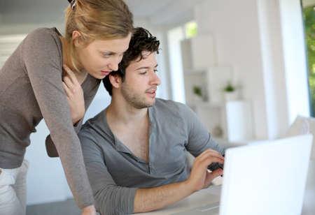 pareja en casa: Los j�venes que estudian desde casa con el ordenador port�til