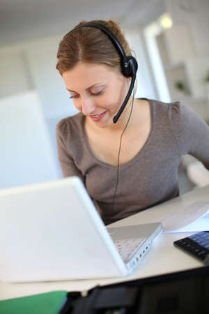 Young woman working from home with laptop and headset photo