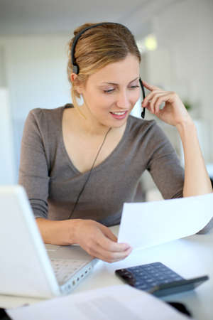 telework: Young woman working from home with laptop and headset Stock Photo