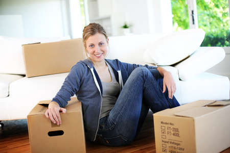 Young girl sitting by cardboards in new home photo