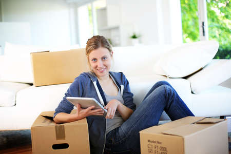 moving company: Young girl websurfing on tablet in new flat Stock Photo