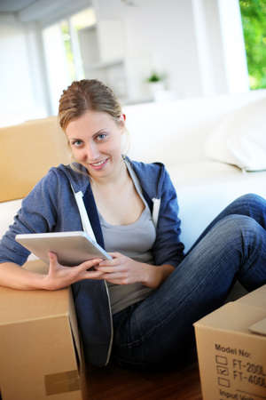 Young girl websurfing on tablet in new flat Stock Photo - 14102894
