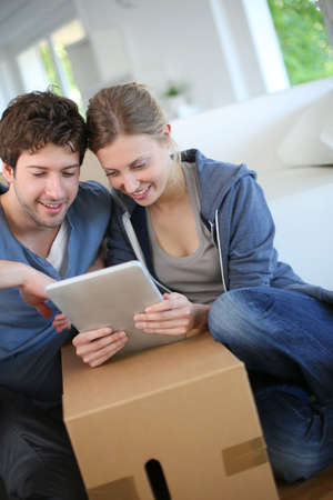 Young couple using tablet to find transport company photo