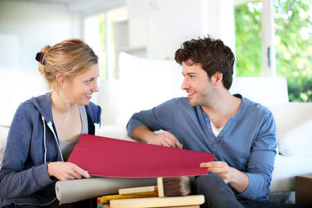 reforming: Young couple choosing wallpaper color for new apartment