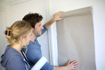 Young couple choosing color of all paper in new home photo