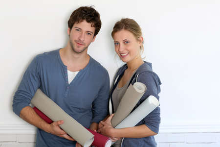 reforming: Portrait of young couple holding wallpaper rolls