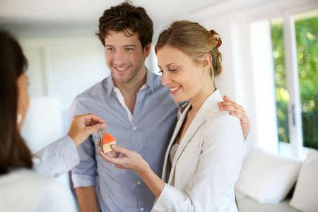 Gelukkig jong koppel krijgt sleutels van hun nieuwe huis Stockfoto