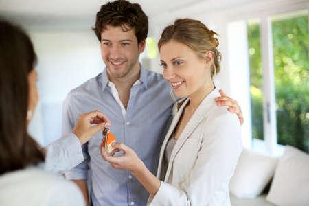 vendedores: Feliz pareja joven obtener las claves de su nuevo hogar Foto de archivo