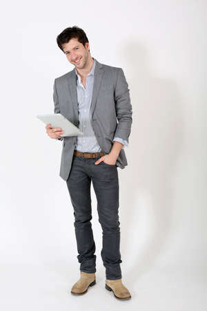 electronic tablet: Young man standing on white background with tablet Stock Photo