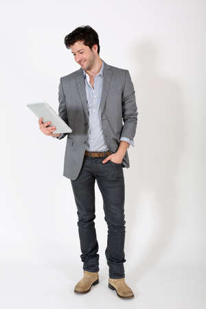 casual caucasian: Young man standing on white background with tablet Stock Photo