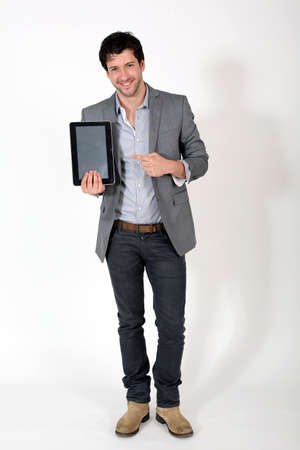 publicity: Young cheerful guy holding electronic tablet Stock Photo