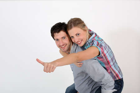 Young man carrying girlfriend on his back photo