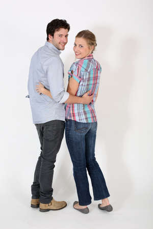 turn back: Young cute couple standing on white background