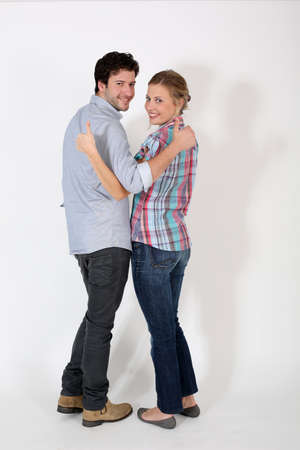 Young couple showing thumbs up on white background photo