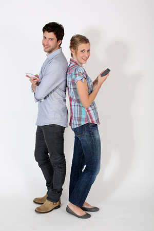 Young couple standng back to back with mobilephone photo
