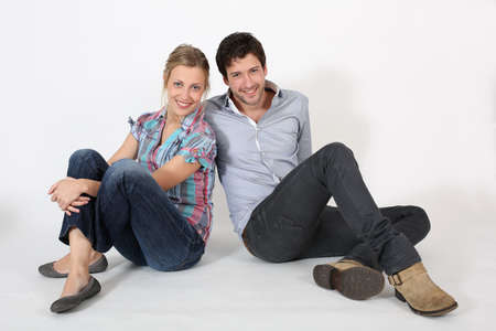 Young couple of students sitting on the floor photo