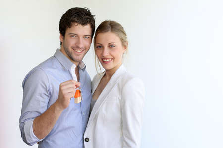 buyers: Young smiling couple holding keys of their new house Stock Photo