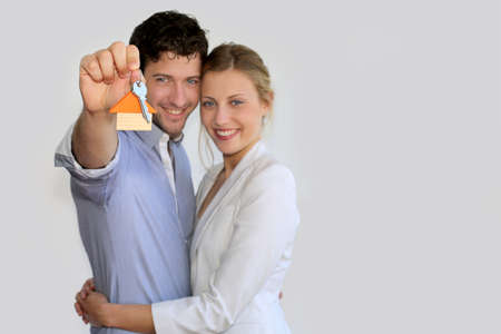 property owners: Young smiling couple holding keys of their new house Stock Photo