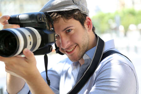 hobby: Portrait of young photographer holding camera Stock Photo