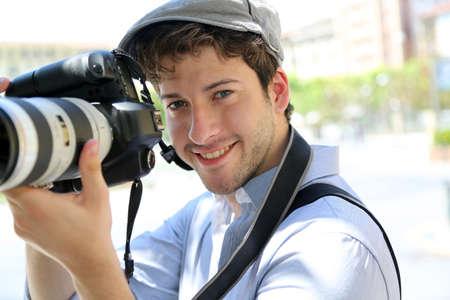 Portret van jonge fotograaf deelneming camera Stockfoto
