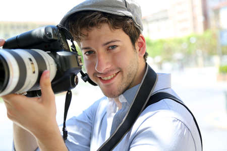 amateur: Retrato del fot�grafo joven que sostiene la c�mara Foto de archivo