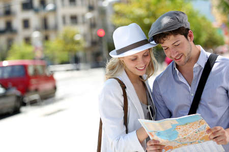 Trendy young couple in town with touristic map photo