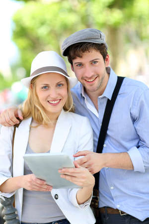 Young couple in town using electronic tablet photo