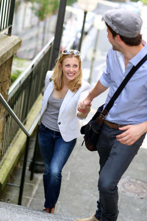 Young romantic couple climbing stairs in town photo