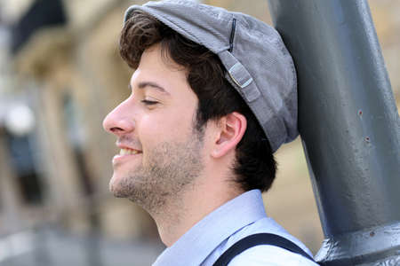 Closeup of young cheerful man wearing hat photo