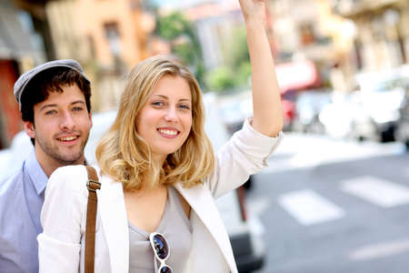 Young couple hailing for a taxi cab photo