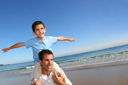 stretched: Father holding son on his shoulders at the beach