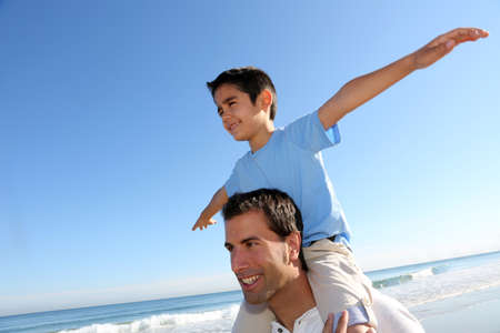 latin child: Father holding son on his shoulders at the beach