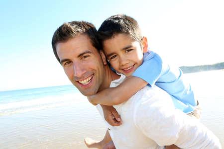 otec: Otec drží syna na ramenou na pláži