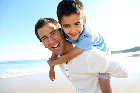 father and son: Father holding son on his shoulders at the beach