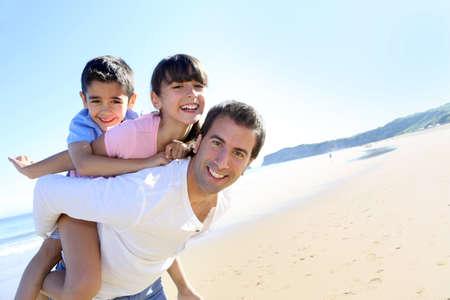 Papa vervoeren van kinderen op zijn rug op het strand
