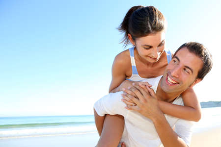 Man carrying girlfriend on his back at the beach photo