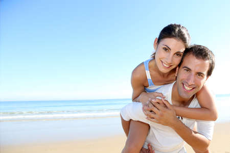carrying girlfriend: Man carrying girlfriend on his back at the beach