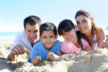 La familia de cuatro que pone en una playa de arena Foto de archivo