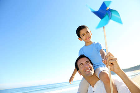 latin child: Little boy up on his fatherss shoulders holding swirl