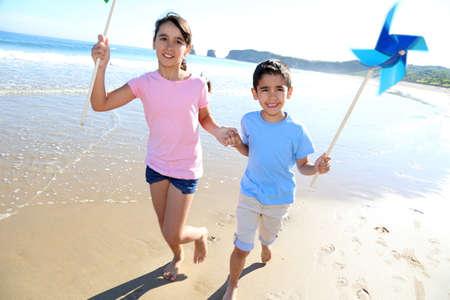 Kids running on the beach with swirls photo
