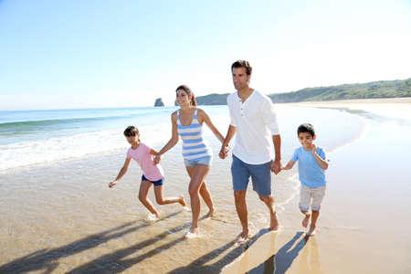 家庭: 家庭有樂趣在海灘上運行