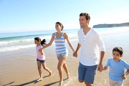 Familia que se divierten corriendo en la playa