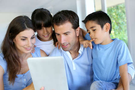 Parents and children using electronic tablet at home photo
