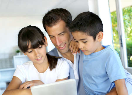 electronic tablet: Father and kids websurfing on digital tablet  Stock Photo