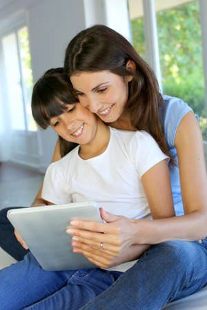 Mother and daughter websurfing on internet with tablet photo